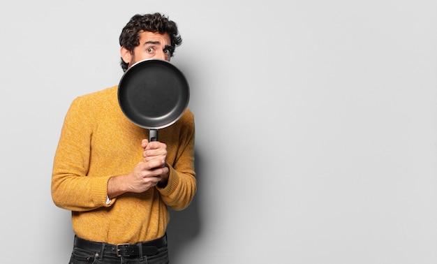 Jonge gekke bebaarde man met een pan. koken concept