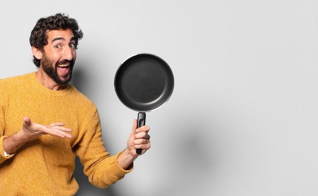 Jonge gekke bebaarde man met een pan. kook concept