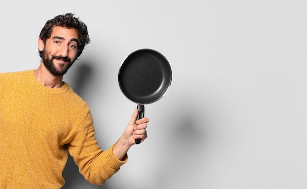 Jonge gekke bebaarde man met een pan