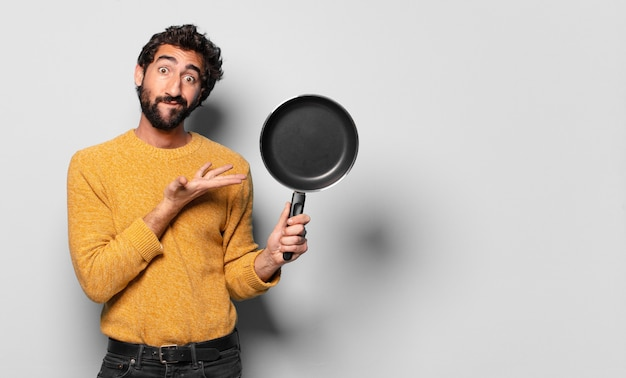 Jonge gekke bebaarde man met een pan.
