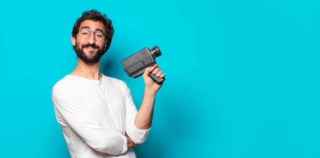 Jonge gekke bebaarde man met een super 8 camera
