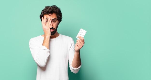 Jonge gekke bebaarde man met een tablet pillen