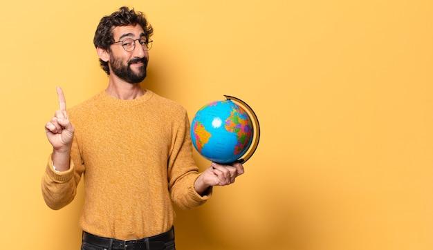 Jonge gekke bebaarde man met een wereldbol kaart.