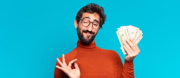 Jonge gekke bebaarde man trotse uitdrukking. dollar biljetten concept