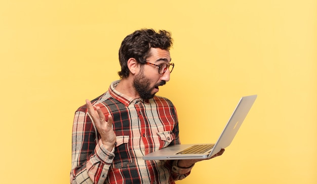 Jonge gekke bebaarde man verraste uitdrukking en een laptop