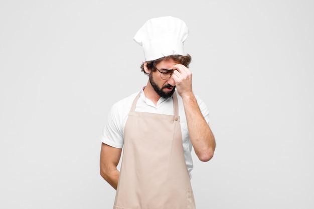 Jonge gekke chef-kok voelt zich gestrest, ongelukkig en gefrustreerd, raakt het voorhoofd en lijdt aan migraine met ernstige hoofdpijn tegen de witte muur