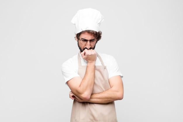 Jonge gekke chef-kok voelt zich serieus, attent en bezorgd, starend zijwaarts met de hand tegen de kin gedrukt tegen de witte muur
