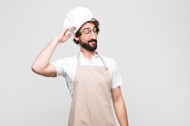 Jonge gekke chef-kok voelt zich verbaasd en verward, krabt zijn hoofd en kijkt naar de zijkant over de witte muur
