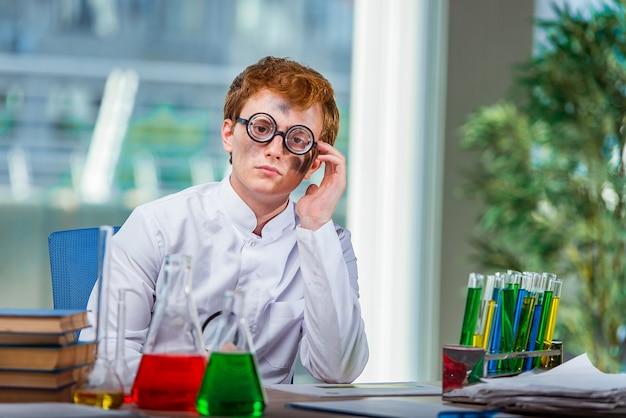 Jonge gekke chemicus die in het laboratorium werkt