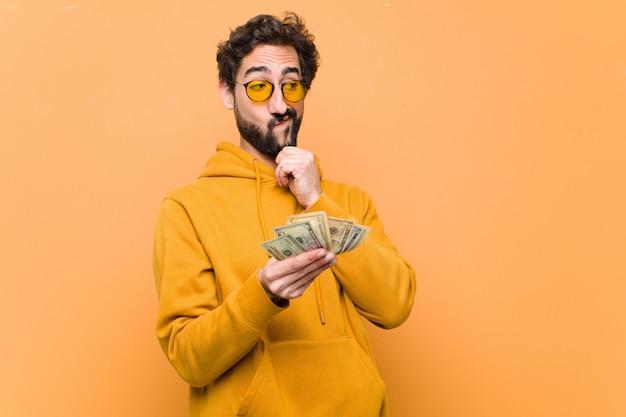 Jonge gekke cool man met dollar biljetten tegen oranje muur