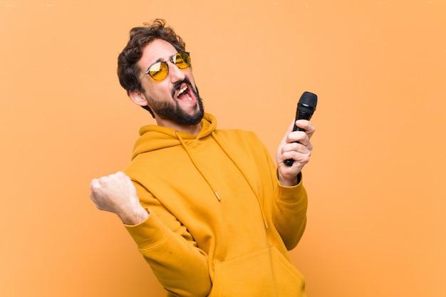 Jonge gekke cool man met een microfoon tegen oranje muur