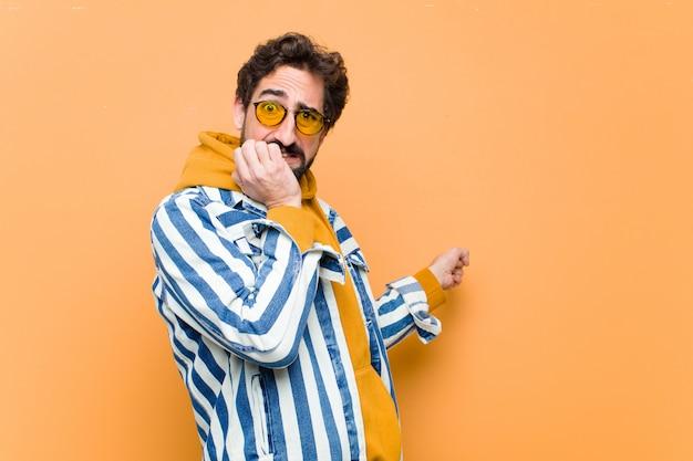 Jonge gekke cool man wijst naar de kant tegen oranje muur