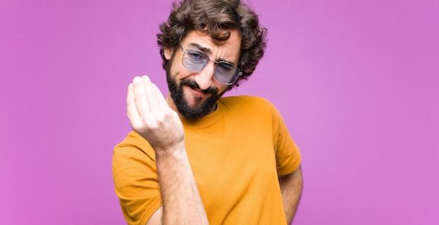 Jonge gekke coole man die capice of geldgebaar maakt en zegt dat je je schulden moet betalen! over muur