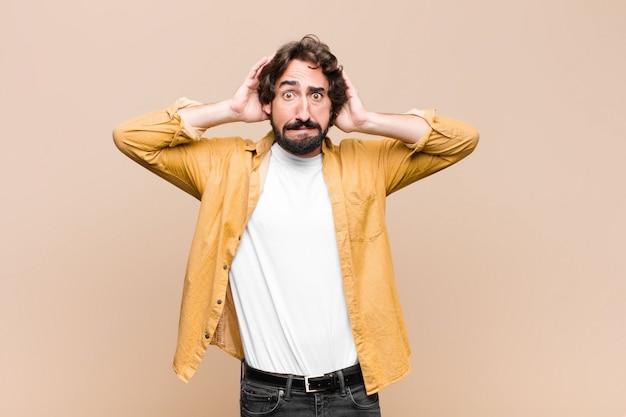 Jonge gekke coole man die zich gestrest, bezorgd, angstig of bang voelt, met de handen op het hoofd, in paniek bij een fout tegen een vlakke muur
