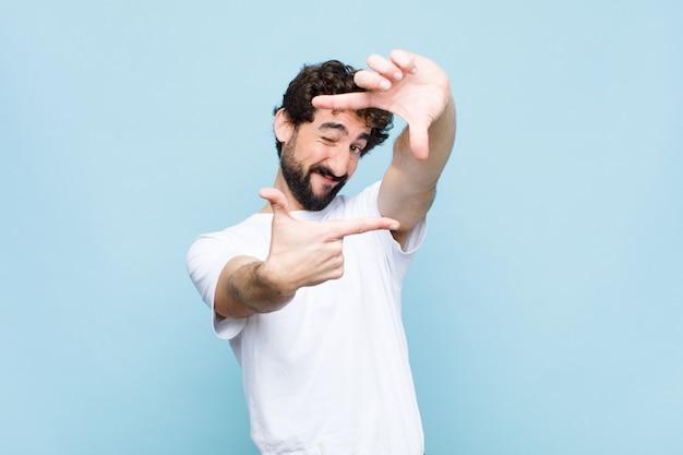 Jonge gekke gebaarde mens die gelukkig, vriendschappelijk en positief voelt, glimlachend en het maken van een portret of een fotokader met handen tegen vlakke muur