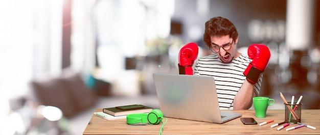 Jonge gekke grafische ontwerper op een bureau met laptop