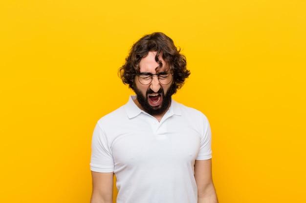 Jonge gekke man die agressief schreeuwt, heel boos, gefrustreerd, verontwaardigd, geërgerd kijkt en geen gele muur schreeuwt