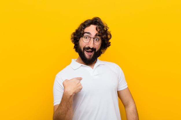Jonge gekke man die blij, trots en verrast kijkt, vrolijk naar zichzelf wijst, een zelfverzekerde en verheven gele muur voelt