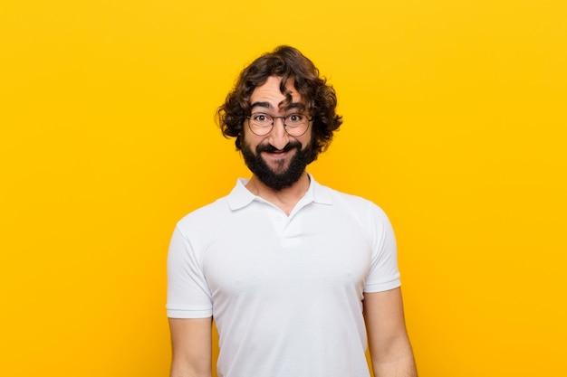 Jonge gekke man die gelukkig en mal met een brede, leuke, gekke glimlach en ogen wijd open gele muur kijkt