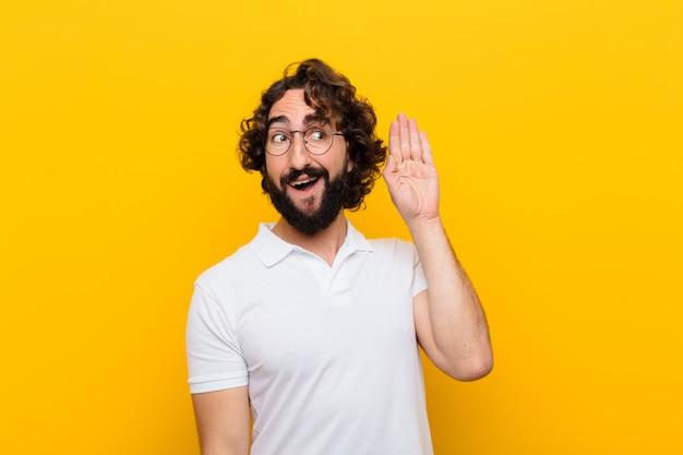 Jonge gekke man die lacht, nieuwsgierig naar de zijkant kijkt, probeert te luisteren naar roddel of een geheim afluistert tegen de gele muur