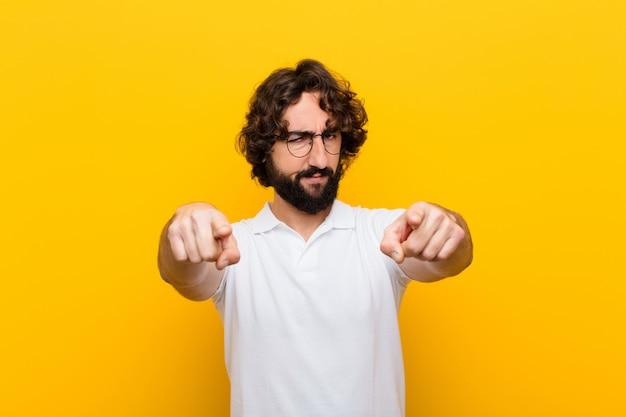 Jonge gekke man die naar de camera met beide vingers en boze uitdrukking wijst en je vertelt je plicht gele muur te doen