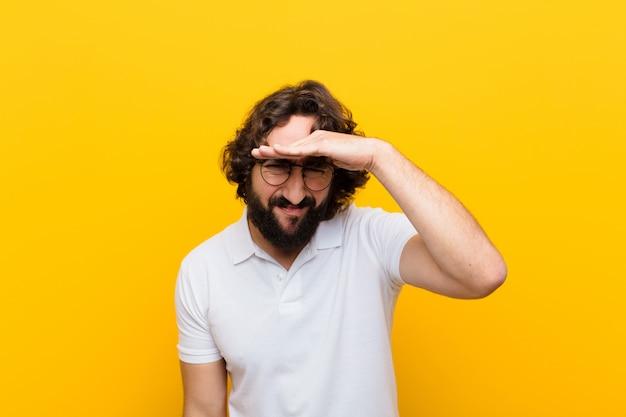 Jonge gekke man die verbijsterd en verbaasd kijkt, met hand voorhoofd ver weg kijkt, let op of gele muur zoekt