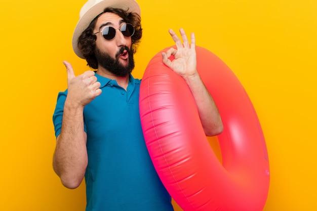 Jonge gekke man die zich gelukkig, verbaasd, tevreden en verrast voelt, ok toont en duimen omhoog gebaren, glimlachend tegen oranje muur