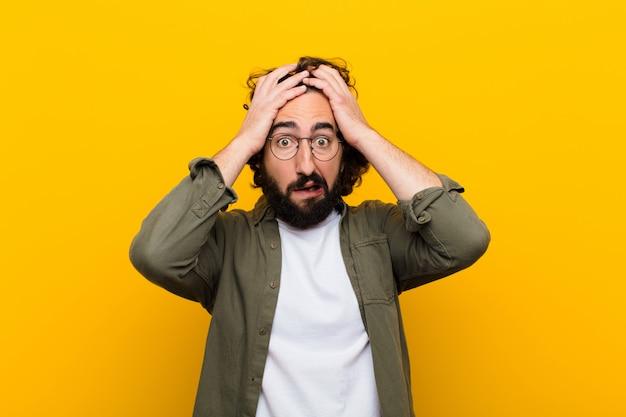 Jonge gekke man die zich geschokt en geschokt voelt, handen opheft en in paniek raakt bij een fout gele muur