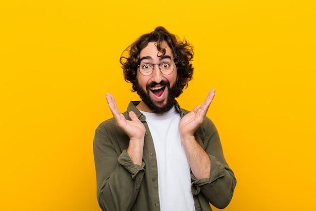 Jonge gekke man die zich geschokt en opgewonden, lachend, verbaasd en gelukkig voelt vanwege een onverwachte verrassing
