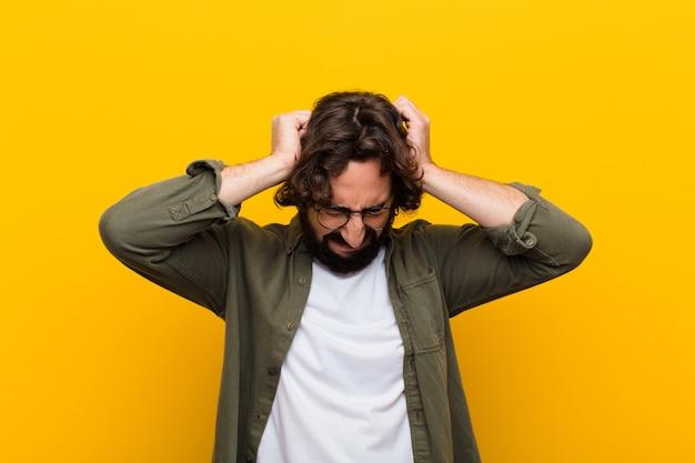 Jonge gekke man die zich gestrest en gefrustreerd voelt, handen opheft, moe, ongelukkig en met migraine tegen de gele muur voelt