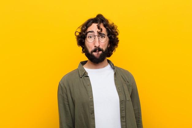 Jonge gekke man die zich verdrietig en gestrest voelt, overstuur vanwege een slechte verrassing, met een negatieve, angstige blik tegen de gele muur