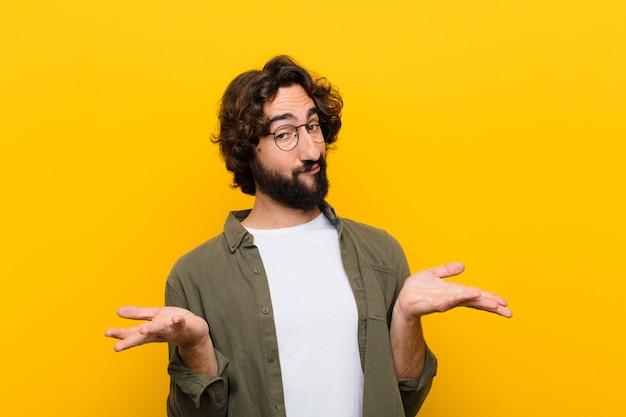 Jonge gekke man die zich verward en verward voelt, onzeker over het juiste antwoord of besluit, en probeert een keuze te maken tegen de gele muur