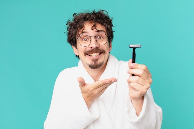 Jonge gekke man die zijn baard scheert met een scheermes