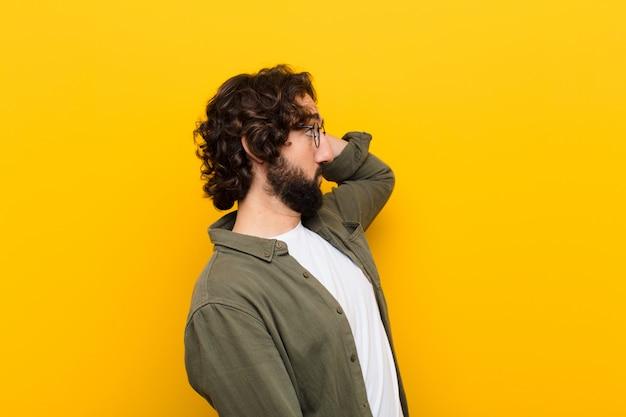Jonge gekke man gevoel geen idee en verward, denken een oplossing, met hand op heup en andere op hoofd, achteraanzicht gele muur