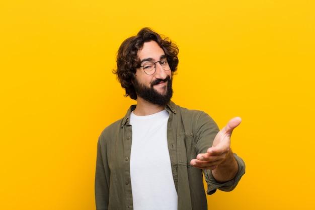 Jonge gekke man glimlachend, gelukkig, zelfverzekerd en vriendelijk, biedt een handdruk om een deal te sluiten, samen te werken