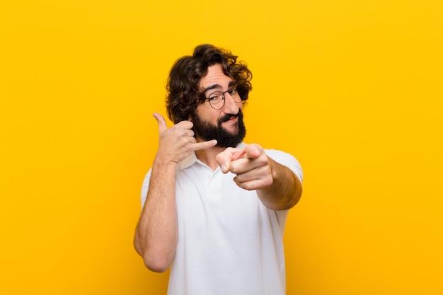 Jonge gekke man glimlachend vrolijk en wijzend naar de camera tijdens het bellen u later gebaar, praten over telefoon gele muur