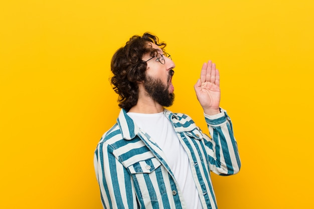 Jonge gekke man luid en boos schreeuwen naar copyspace aan de zijkant, met de hand naast de mond tegen de gele muur
