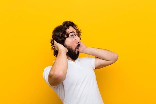Jonge gekke man met open mond, die geschokt en geschokt kijkt vanwege een vreselijke fout, die zijn handen opheft naar de gele muur