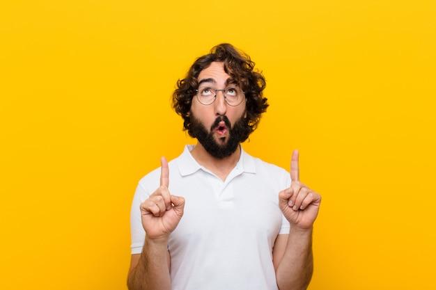 Jonge gekke man op zoek geschokt, verbaasd en met open mond, naar boven wijzend met beide handen om ruimte gele muur te kopiëren
