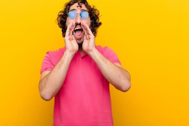 Jonge gekke man voelt zich blij, opgewonden en positief, geeft een grote schreeuw met handen naast de mond, roept oranje muur