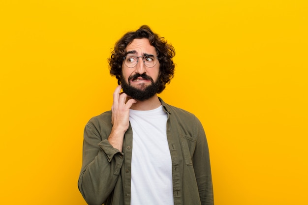 Jonge gekke man voelt zich gestrest, gefrustreerd en moe, wrijft pijnlijke nek, met een bezorgde, onrustige blik gele muur