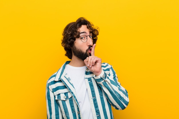 Jonge gekke man vraagt om stilte en stilte, gebaart met vinger voor mond, zegt shh of houdt een geheim tegen gele muur
