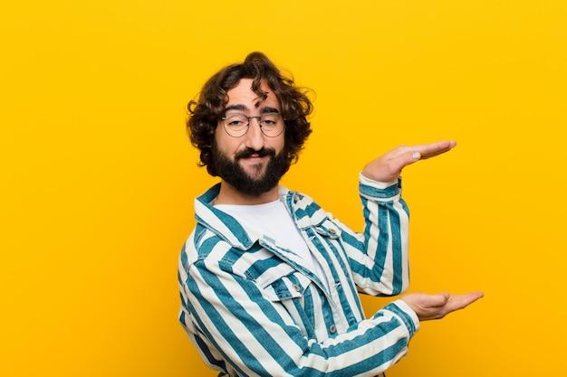 Jonge gekke mens die een voorwerp met beide handen aan kant copyspace houden, tonen, die een objecten gele muur aanbieden