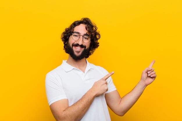 Jonge gekke mens die gelukkig glimlacht en aan kant en omhoog met beide handen richt die voorwerp in copyspace gele muur toont