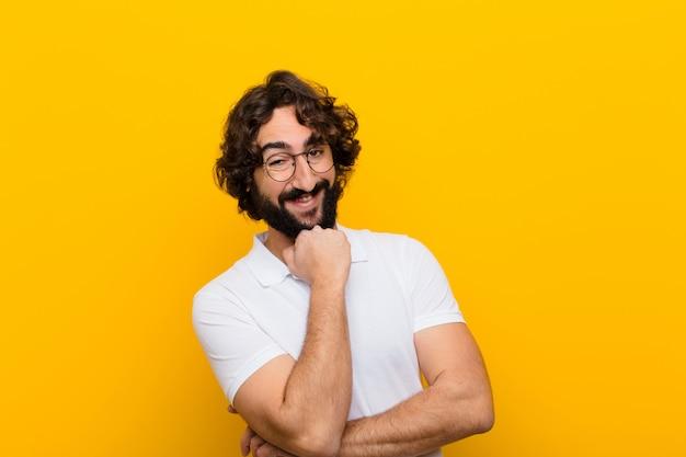 Jonge gekke mens die, genietend van het leven, gelukkig, vriendelijk, tevreden en zorgeloos met hand op kin gele muur glimlacht