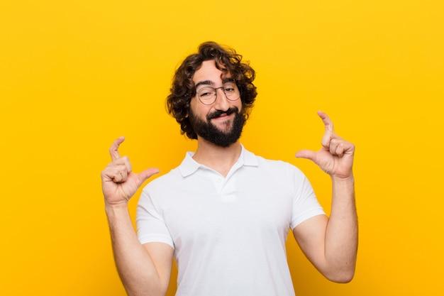 Jonge gekke mens die of eigen glimlach met beide handen ontwerpen, schetsen die positief en gelukkig, wellness tegen gele muur kijken
