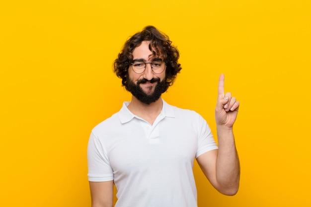 Jonge gekke mens die vrolijk en gelukkig glimlacht, naar omhoog met één hand richt om ruimte tegen gele muur te kopiëren