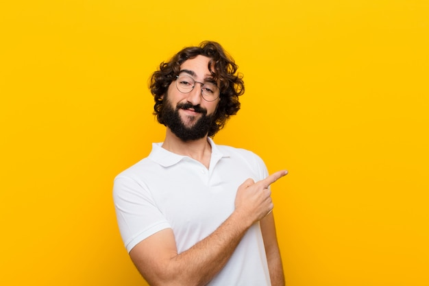 Jonge gekke mens die vrolijk glimlachen, gelukkig voelen en aan de kant en naar omhoog richten, voorwerp in exemplaar ruimte gele muur tonen