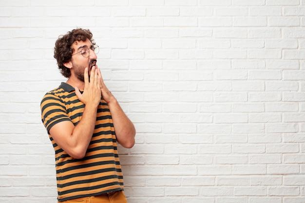 Jonge gekke of dwaze mens die en emoties tegen bakstenen muurachtergrond gesturing uitdrukken