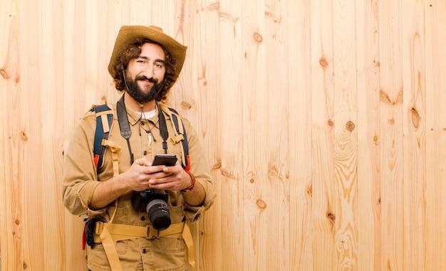 Jonge gekke ontdekkingsreiziger met strohoed en rugzak op houten achtergrond